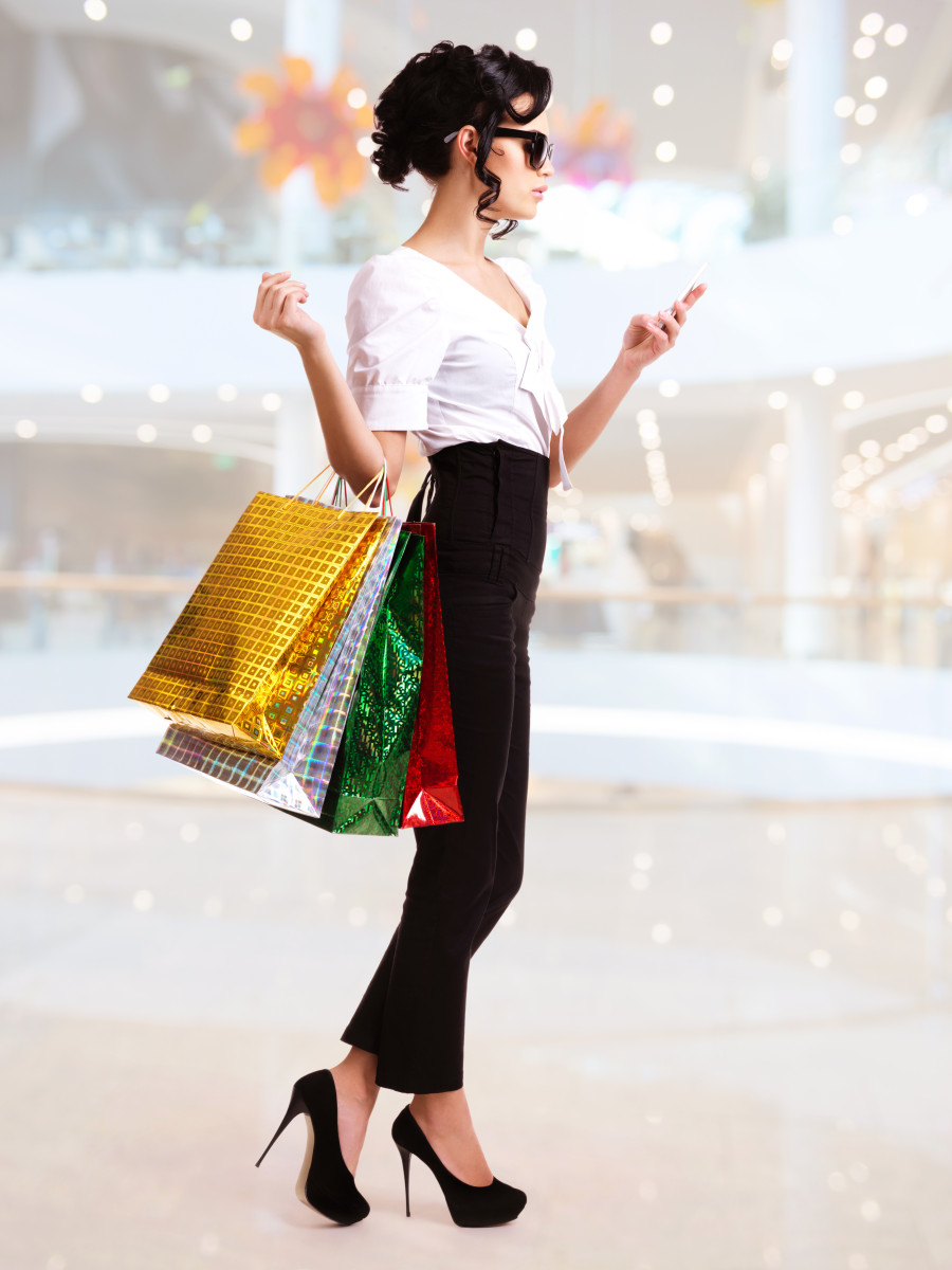Portrait of happy woman with color shopping bags.